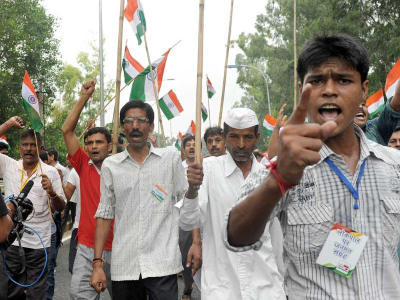 Supporters of social activist Anna Hazare shout slogans as they stage a protest after his arrest in New Delhi.