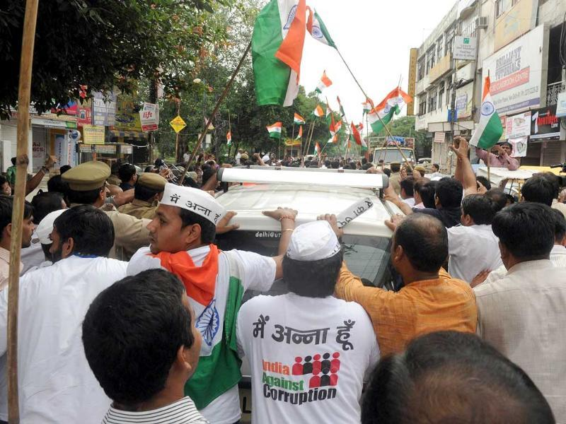 Supporters of social activist Anna Hazare surround a police vehicle in New Delhi, which is carrying the activist after his arrest by police authorities.