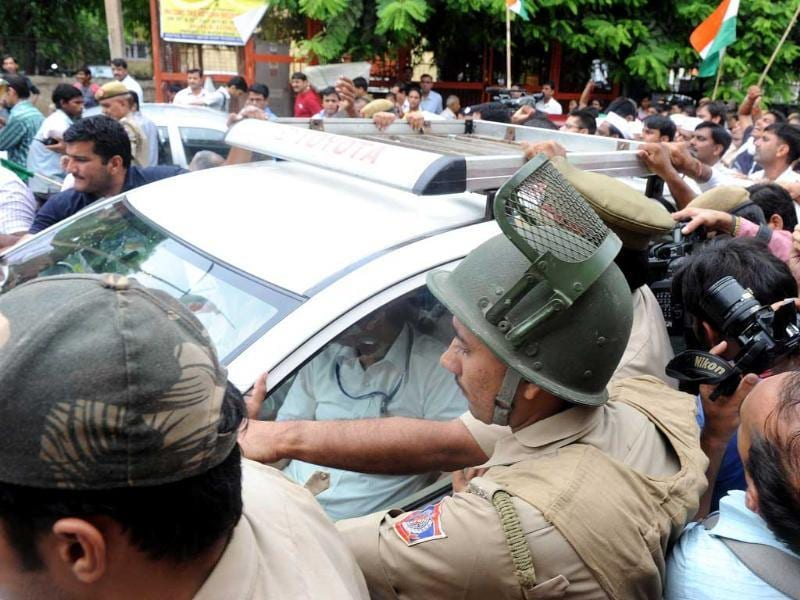 Supporters of social activist Anna Hazare surround a police vehicle in New Delhi which is carrying the activist after his arrest by police authorities.