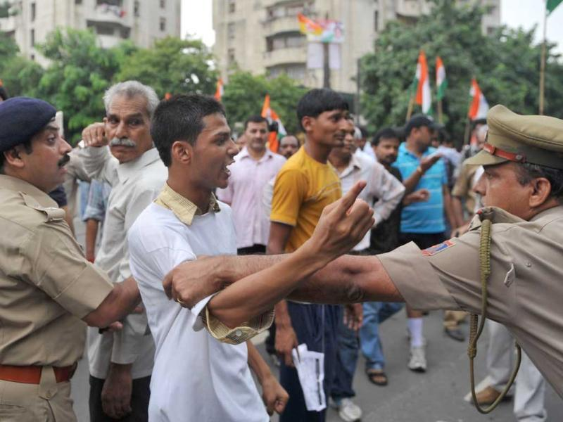 Supporters of Anna Hazare argue with police officers after his arrest in New Delhi.