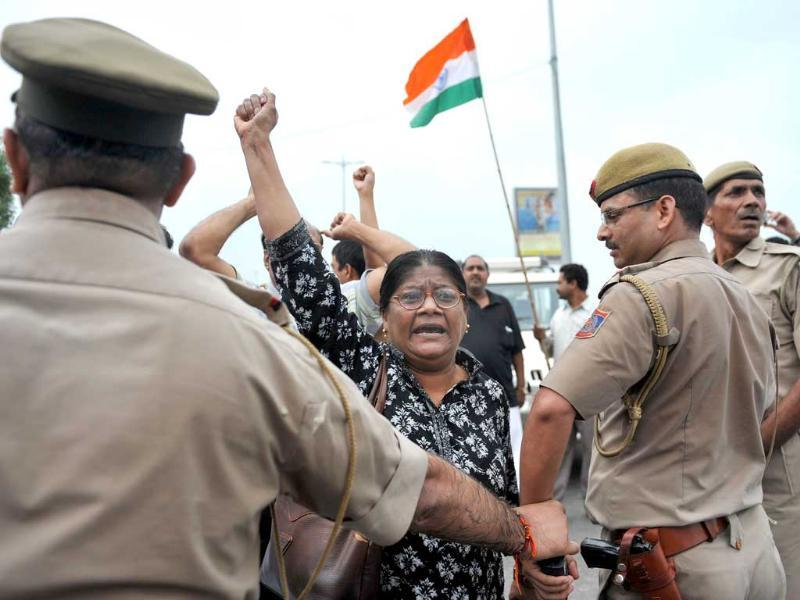 Policemen control supporters of Anna Hazare after his arrest in New Delhi.