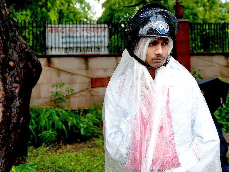 A supporter of Anna Hazare covers himself with a plastic sheet as he waits outside JP Park in New Delhi.