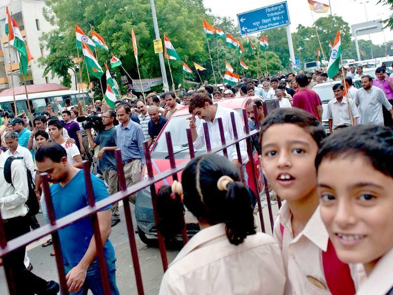 Schoolchildren (R) look on as supporters of Anna Hazare shout slogans after his arrest in New Delhi.