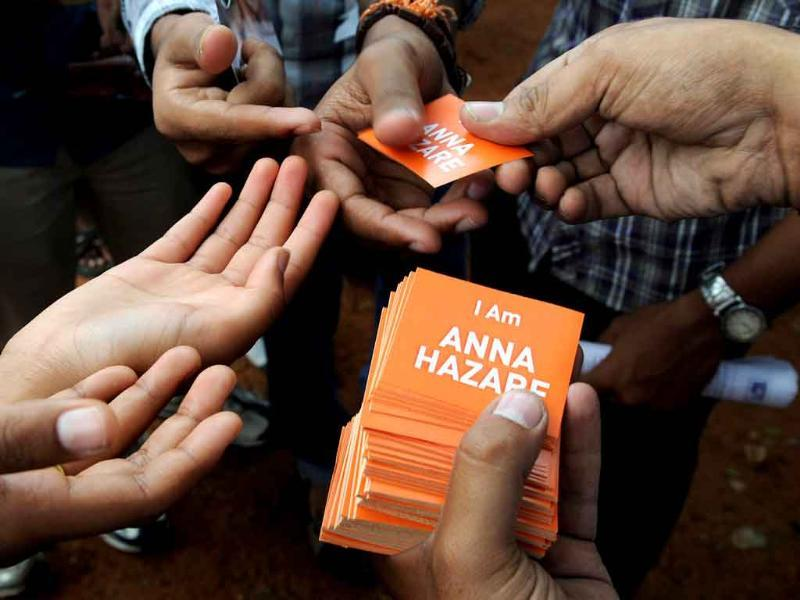 A supporter of Anna Hazare's mass movement on anti-corruption distributes stickers to volunteers during a rally at Freedom Park in Bangalore.