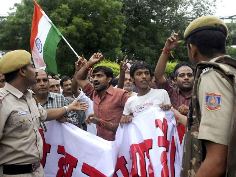 Supporters of Anna Hazare shout anti-government slogans as they are restrained by police personnel during a protest rally in New Delhi.