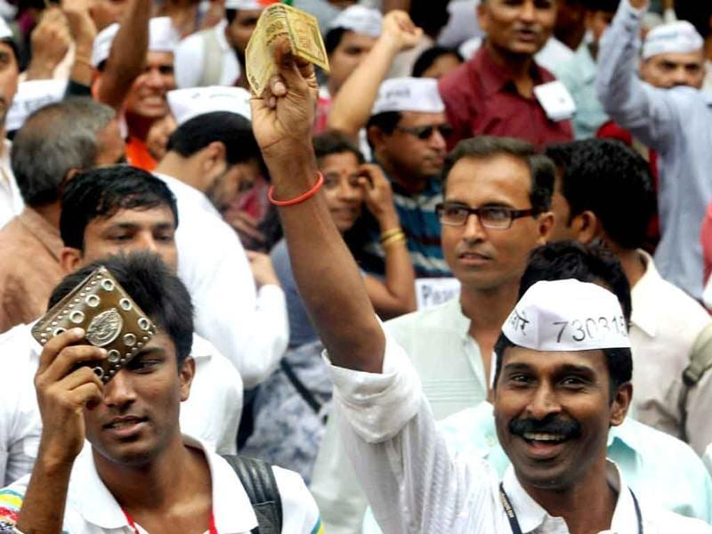Supporters of Anna Hazare show notes during their protest at Azad Maidan in Mumbai.