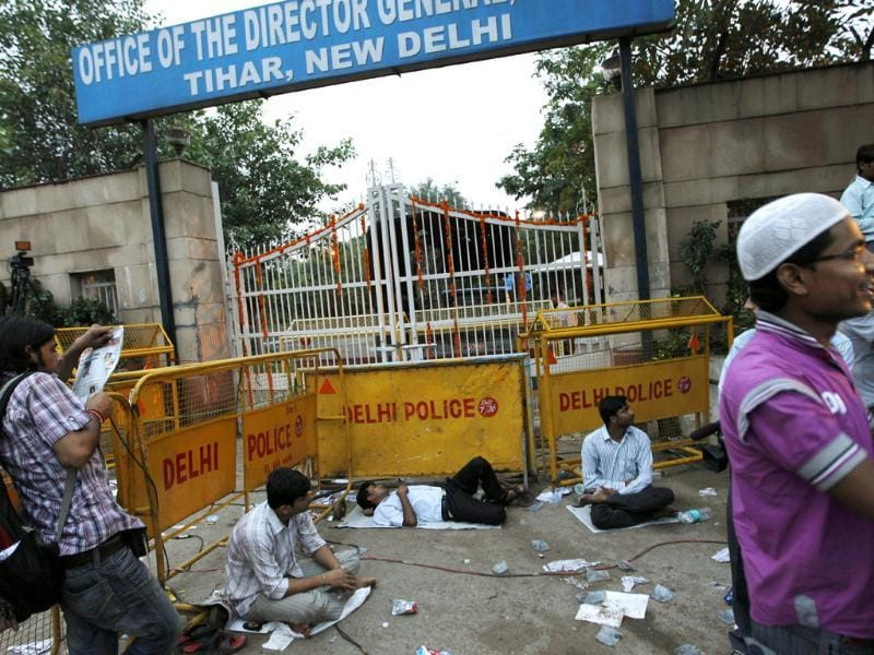 Tired supporters of anti-corruption activist Anna Hazare rest after a night-long vigil outside a gate of Tihar prison to lend their support to his fight against corruption in New Delhi.