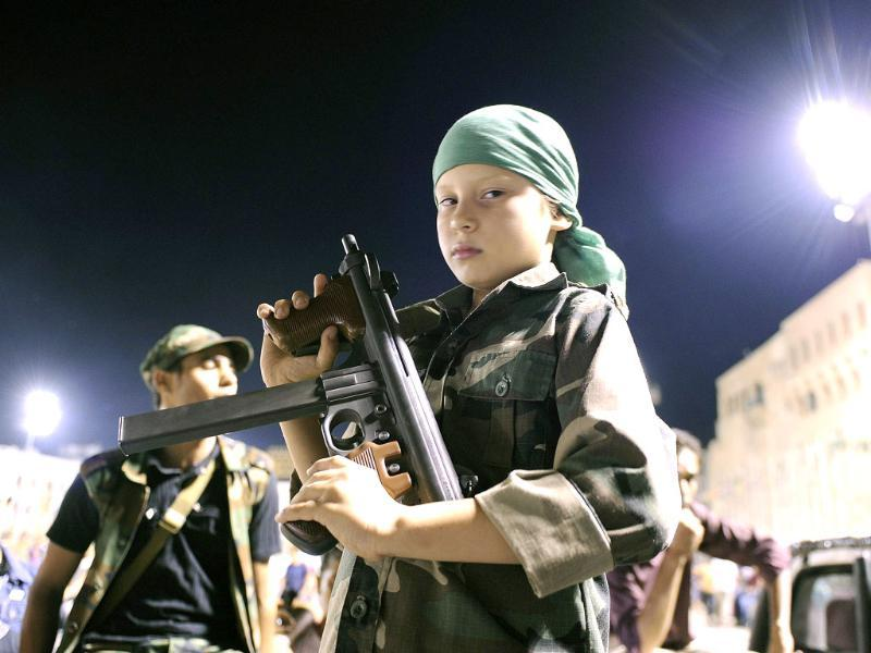 A young boy poses with a gun given to him by adults as supporters of Muammar Gaddafi gather at Green Square in Tripoli.
