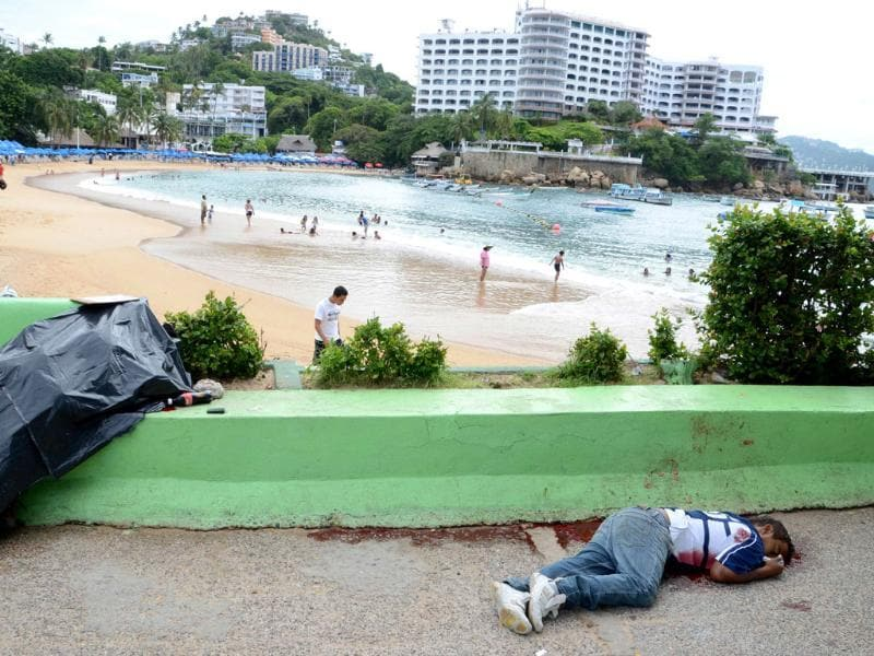 The bodies of two men shot dead next to the Caleta beach in the Pacific resort city of Acapulco, Mexico. Acapulco has been hit by violence as drug gangs continue to battle for control of the region.