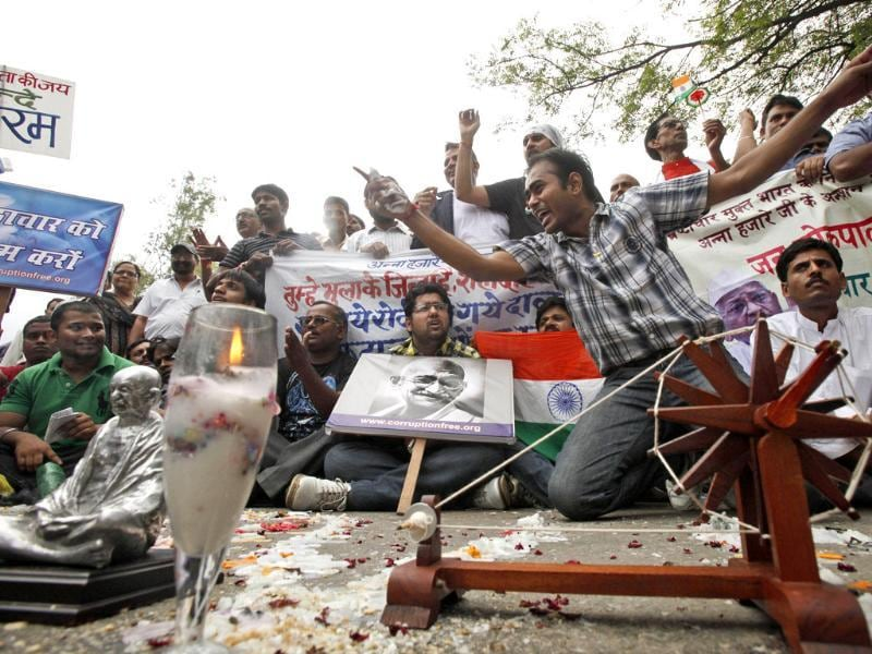 Supporters of anti-corruption activist Anna Hazare raise slogans as they place the a traditional spinning wheel, symbolic of Mahatma Gandhi, outside Tihar jail in New Delhi.
