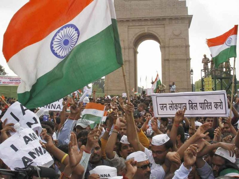 Supporters of social activist Anna Hazare raise national flags during a protest march against corruption in front of India Gate in New Delhi.
