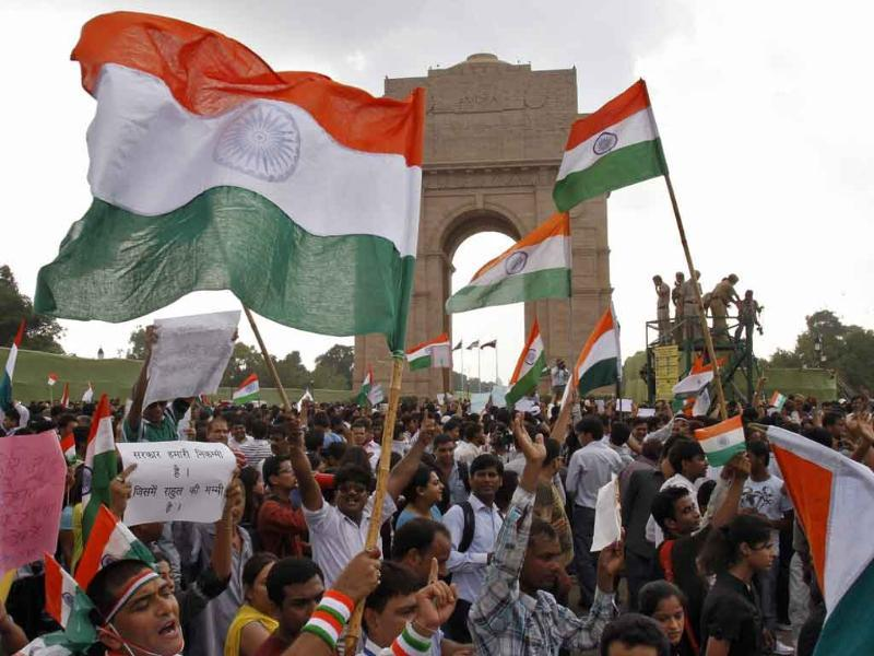Supporters of Anna Hazare raise national flags during a protest march against corruption in front of India Gate in New Delhi.