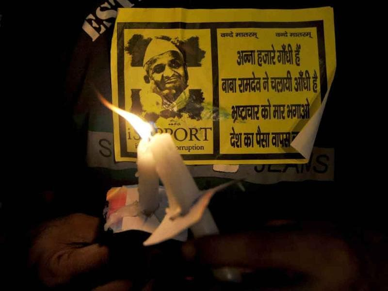 A supporter of social activist Anna Hazare holds lit the candles and a Hazare sticker during a protest in New Delhi.