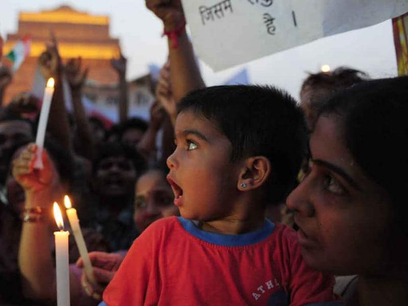 Anna Hazare supporters shout anti-government slogans and hold lighted candles during a rally in his support at India Gate in New Delhi.