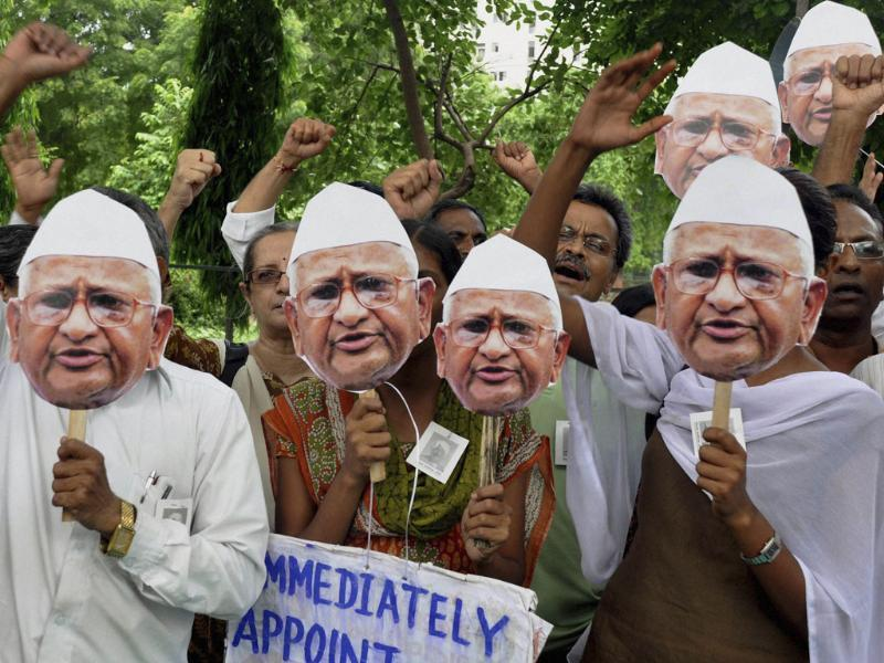 People hold cutouts of anti-corruption activist Anna Hazare and shout slogans during a protest in support of Hazare's fight against corruption in Ahmadabad.