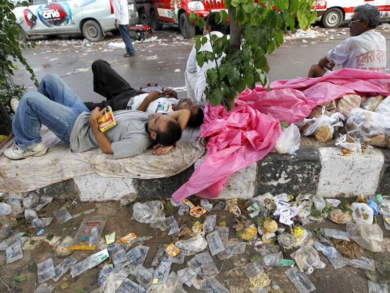 Volunteers rest near leftover food packets after serving supporters of Anna Hazare as they camped outside Tihar prison.