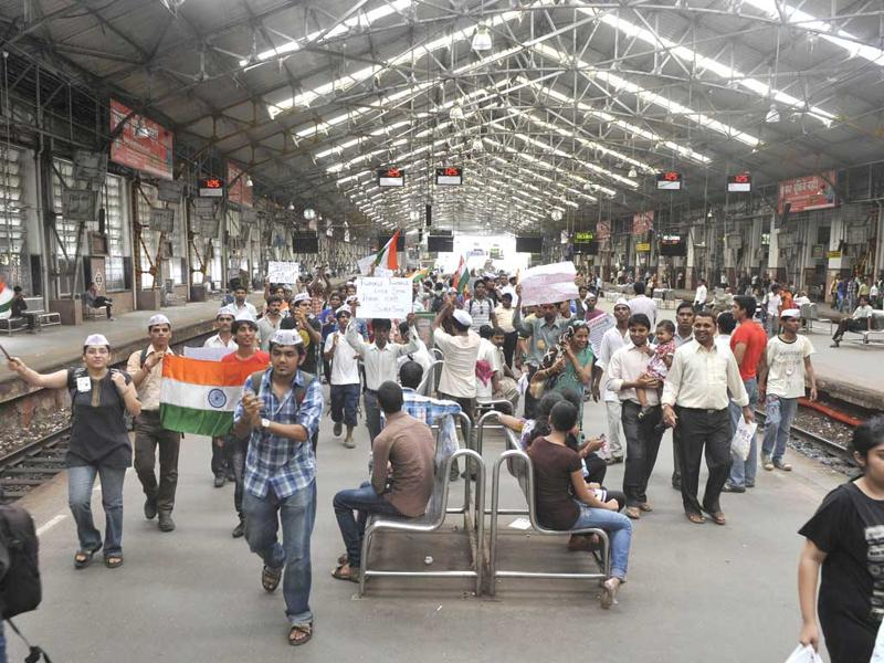 Supporters of Anna Hazare hold flags and placards while shouting slogans as they walk through a railway station in Mumbai.