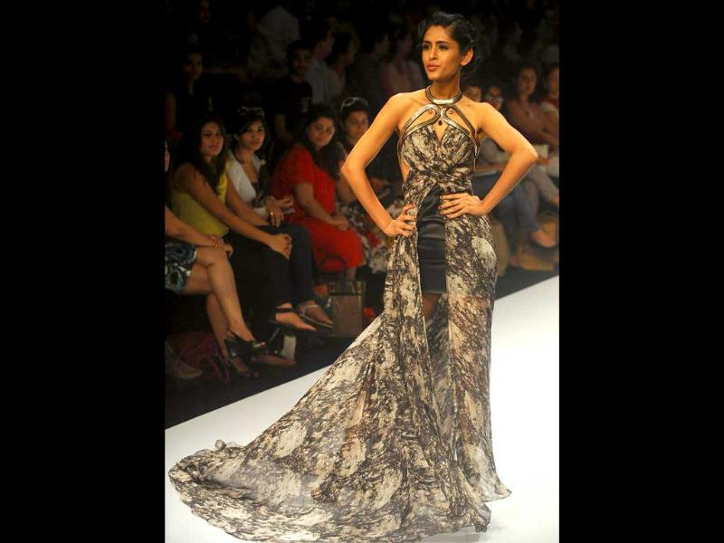 Model poses in Jatin Varma's gown with a trail and slit in front.