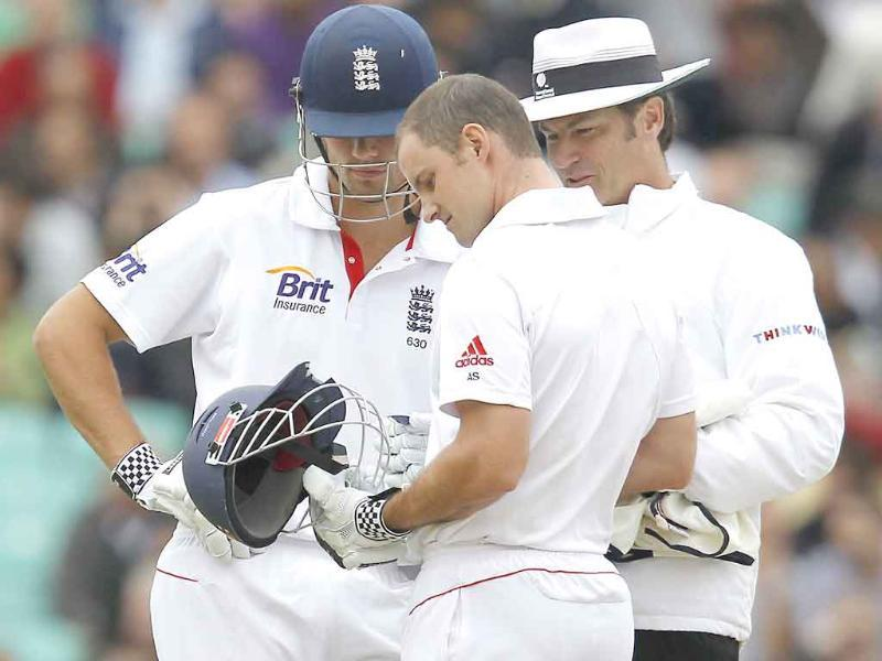 England's captain Andrew Strauss inspects his broken helmet as team-mate Alastair Cook and Australian Umpire Simon Taufel look on after Strauss was hit in the helmet by a bowled ball from Ishant Sharmaat The Oval Cricket Ground in London.