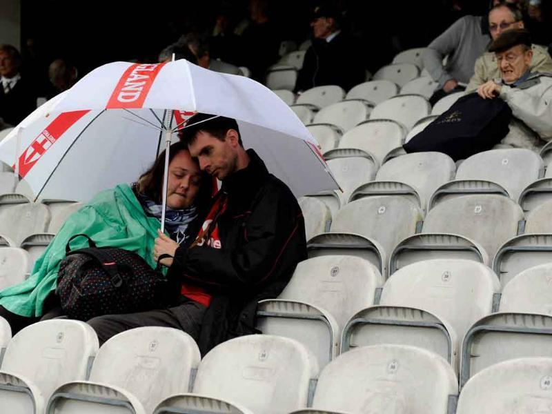 Two spectators take shelter under an umbrella as rain delayed the fourth cricket Test match between England and India at the Oval cricket ground in London.