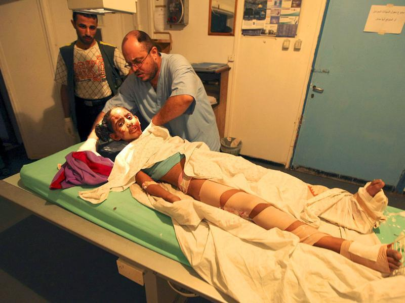 A Palestinian doctor tends to an injured girl at Al-Shifa hospital, after an overnight Israeli air strike, in Gaza City.