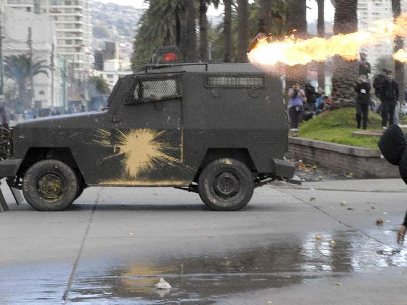 A demonstrator throws a Molotov cocktail at a police vehicle in Valparaiso, Chile.