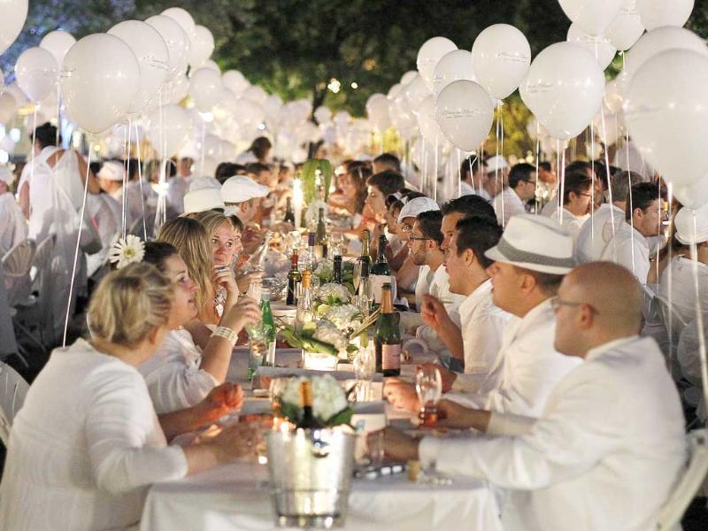 People eat as they participate in the White Dinner in Quebec City. Guests are required to be dressed in white and bring their own food, drink and cutlery.