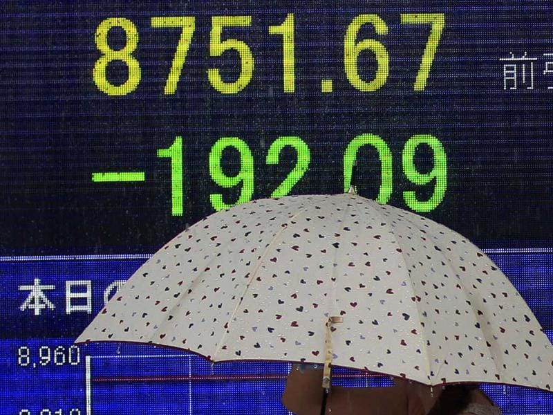 A woman under an umbrella walks past the electronic stock board of a securities firm in Tokyo.