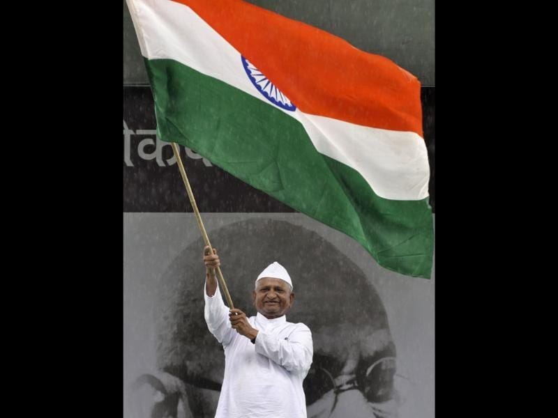 Social activist Anna Hazare waves the national flag at Ramlila grounds in New Delhi. A vast and jubilant crowd cheered as Gandhian activist Hazare walked out of jail in New Delhi.