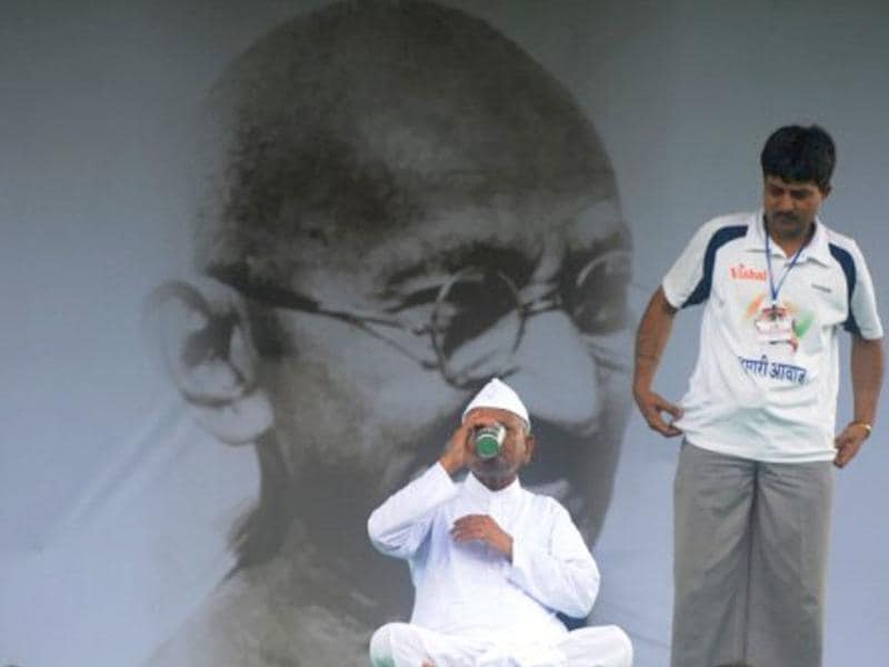 Social activist Anna Hazare (L) drinks as a supporter looks on at Ramlila Grounds in New Delhi.
