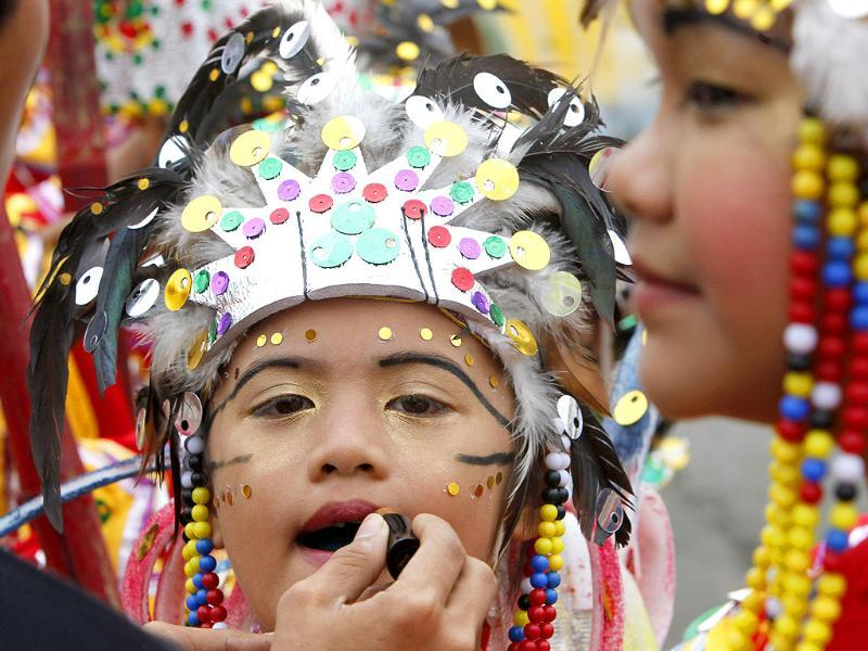 A student has lipstick applied before performing a tribal dance during the Kadayawan festival in Davao city, southern Philippines.