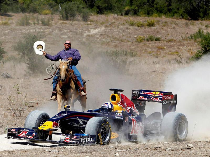Former Formula One driver David Coulthard of Great Britain drives the Red Bull Show Car while being chased by a cowboy at a ranch in Johnson City, Texas.