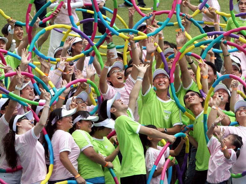 Some of the 2,496 Taiwanese participants celebrate after swinging hula hoops in an attempt to break the Guinness World Record for the most number of people swinging hula hoops in two minutes in Taipei.