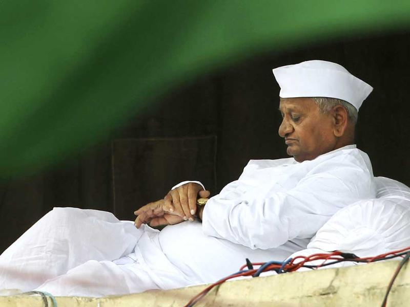 Anna Hazare checks his watch as he sits on the stage during his hunger strike against corruption in New Delhi.