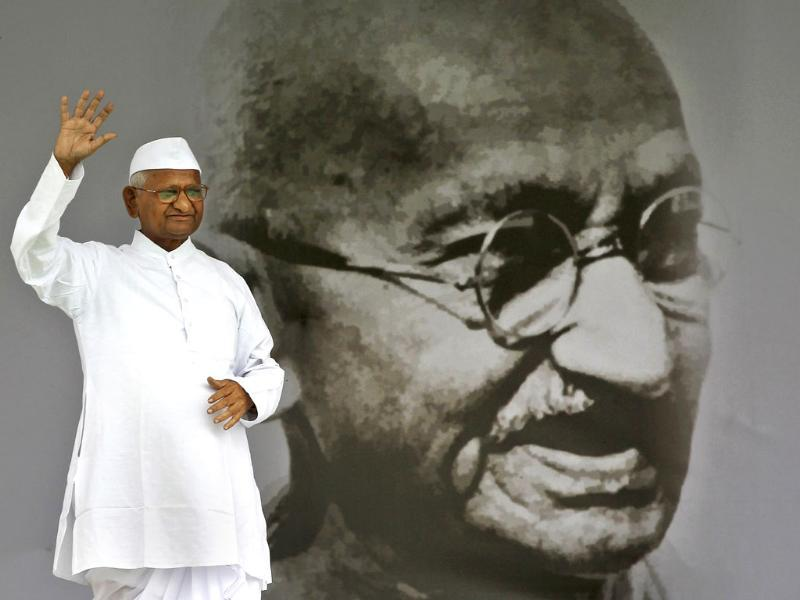 Anti-corruption activist Anna Hazare waves next to a giant portrait of Mahatma Gandhi on the stage during his hunger strike in New Delhi.