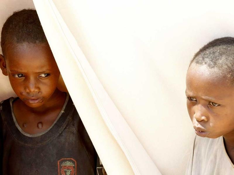 Children sit at the entrance of their tent in a settlement for internally displaced people in Mogadishu.