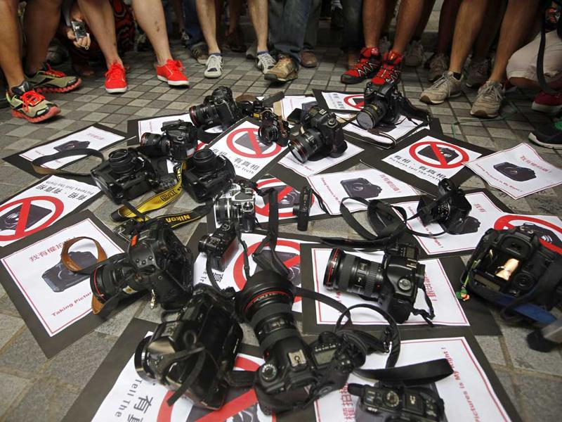 Photo journalists put down their cameras on the ground during a protest outside the police headquarters in Hong Kong.