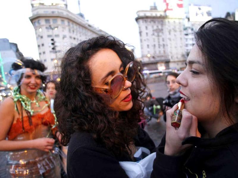 A woman applies lipstick on another as they take part in a SlutWalk rally against sexual abuse and inequality in Buenos Aires.