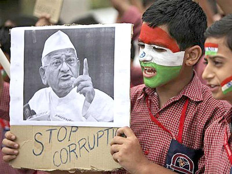 Schoolboys hold a placard in support of anti-corruption activist Anna Hazare during a protest against corruption in Jammu.