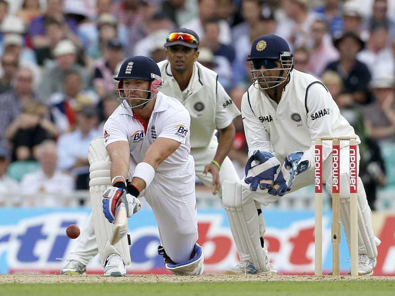 Matt Prior watched by India's Rahul Dravid and Mahendra Singh Dhoni plays a reverse sweep off the bowling of India's Amit Mishra in their fourth test match, at The Oval cricket ground in London.