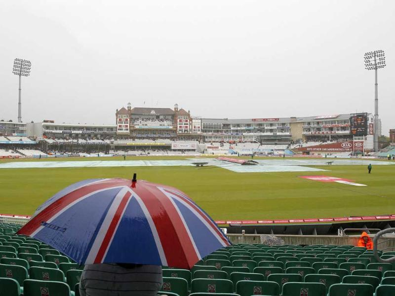 A spectator waits under an umbrella as rain delays play after the lunch interval during day 3 of the fourth Test match between England and India at The Oval Cricket Ground in London.