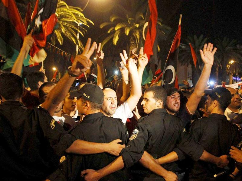 Members of the Libyan community in Tunisia gather outside the Libyan Embassy in Tunis to show support for the rebel fighters who had advanced into Tripoli against Libya's leader Muammar Gaddafi.