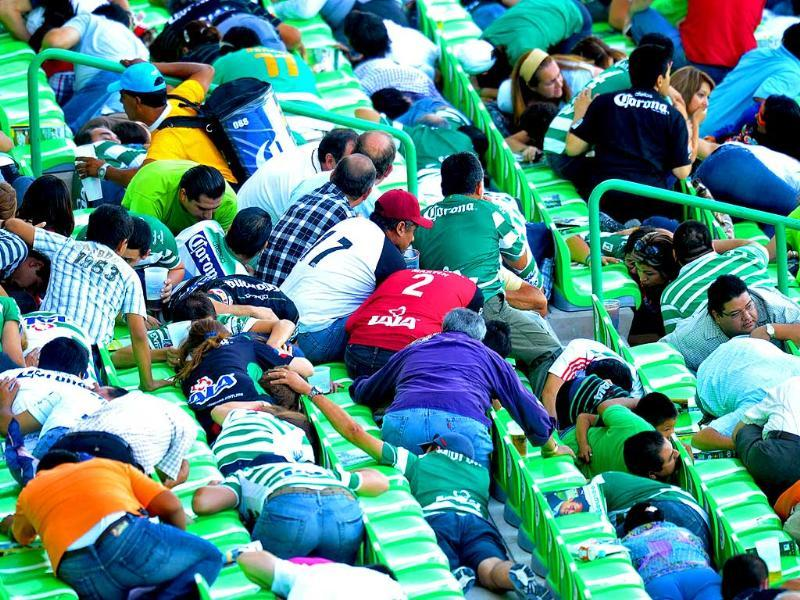 Fans of Santos and Morelia react during the Mexican league championship soccer match after gunshots were heard in the vicinity of the Santos Laguna stadium in Torreon. The soccer match in Mexico's first division was abandoned on Saturday after a shoot-out just outside the stadium shocked players and fans alike in the northern city of Torreon.