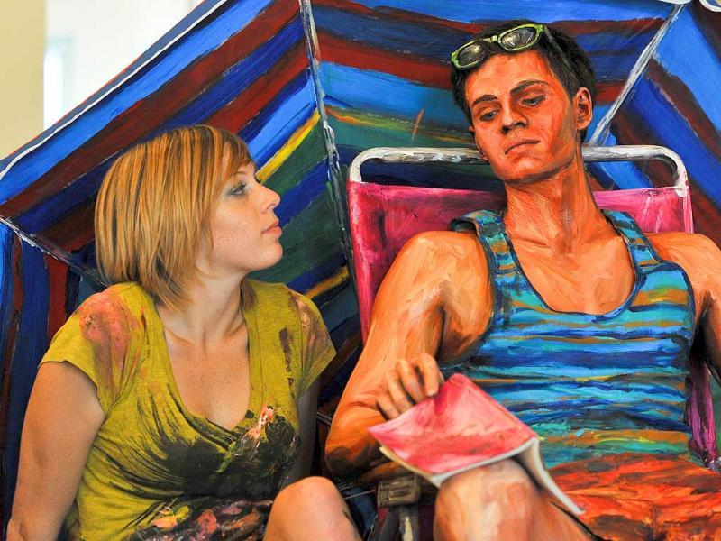 Model Will Claybaugh poses with US artist Alexa Meade after she painted him during a performance at the Irvine Contemporary gallery in Washington. Meade, 24, paints over people so that they look like paintings, then photographs them either in a natural setting or with a painted background.