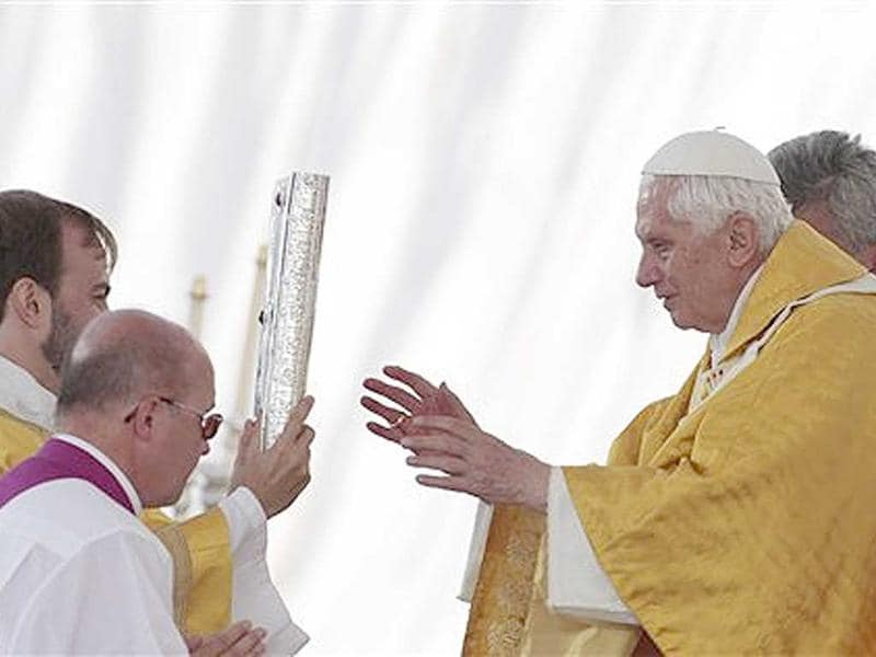 Pope Benedict XVI (R), receives the book of the Gospels as he celebrates a Mass at the Cuatro Vientos airport during the Catholic Church's World Youth Day celebrations, in Madrid.