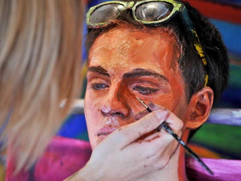 US artist Alexa Meade paints the face of Will Claybaugh's during a performance at the Irvine Contemporary gallery in Washington.