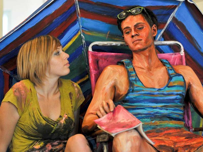 US artist Alexa Meade poses next to model Will Claybaugh's after painting him during a performance at the Irvine Contemporary gallery in Washington.