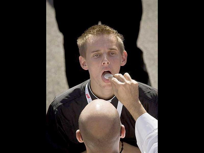 A young man takes communion before the arrival of Pope Benedict XVI, next to the Almudena Cathedral in Madrid.
