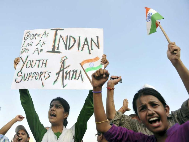 A supporter of anti-corruption activist Anna Hazare holds a placard as others shout slogans during a rally at India Gate in New Delhi.