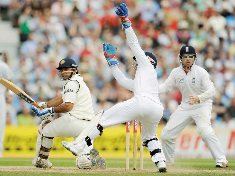Mahendra Singh Dhoni hits the ball past England's Matt Prior (2nd R) as Ian Bell looks on during their fourth cricket Test match at the Oval cricket ground in London.